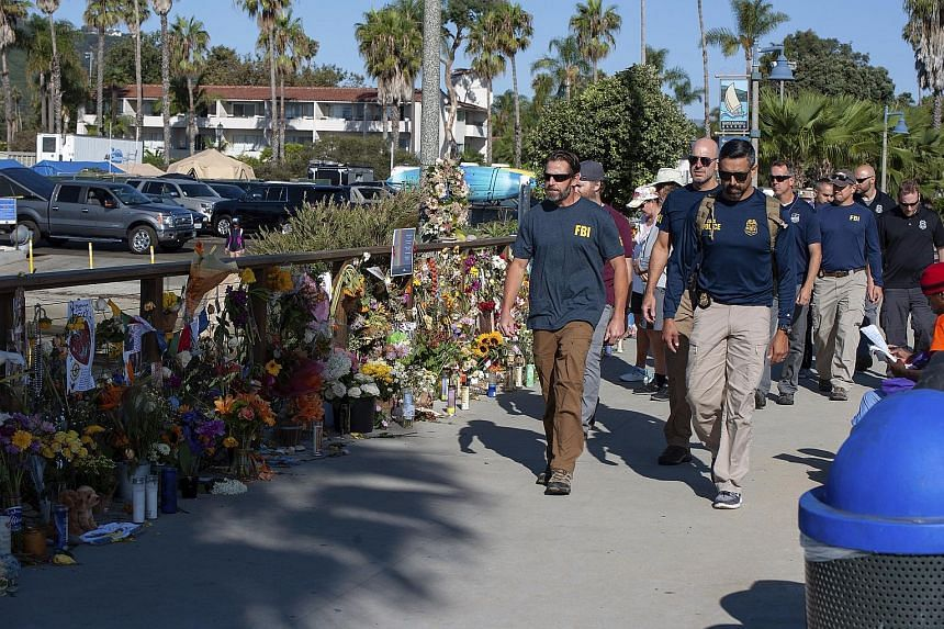 FBI agents walking past a memorial for the 34 victims of the Conception diving boat fire at the Santa Barbara Harbour. The US authorities issued a search warrant at Truth Aquatics' offices in Santa Barbara, California, on Sunday.