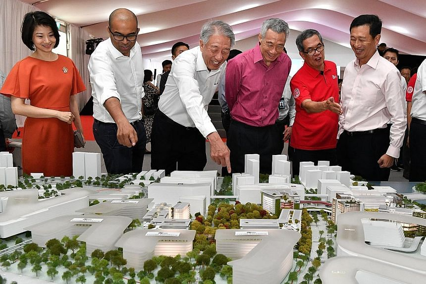 Prime Minister Lee Hsien Loong and Singapore Institute of Technology president Tan Thiam Soon (in red) looking at a model of the future SIT campus in Punggol during the ground-breaking ceremony yesterday. With them are (from left) Senior Parliamentar