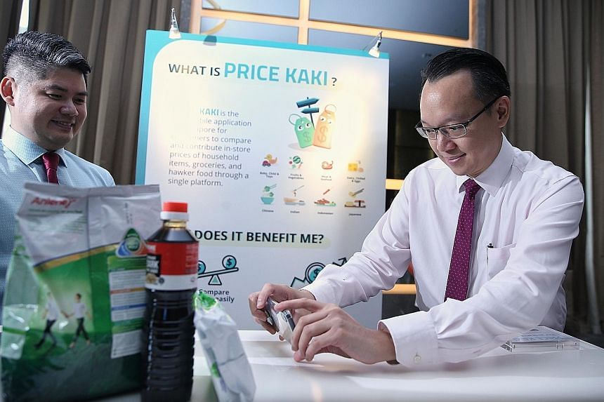 Dr Tan Wu Meng (at right), Senior Parliamentary Secretary for Trade and Industry, trying out the Price Kaki mobile app, developed by the Consumers Association of Singapore (Case), at Case's fund-raiser yesterday. With him was Case's deputy head of ap