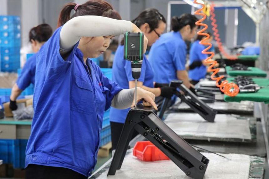 Workers produce desks for export at a factory in Nantong in China's eastern Jiangsu province, on Sept 4, 2019.