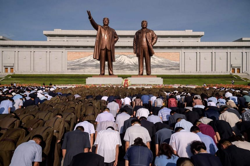 People bow before the statues of the late North Korean leaders Kim Il Sung and Kim Jong Il at Mansu Hill in Pyongyang, on July 8, 2019.
