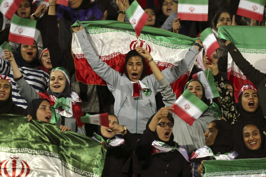 Iranian women wave their country's flag after a rare move by the authorities to allow them into Azadi stadium to watch a soccer match in Teheran on Oct 16, 2018.