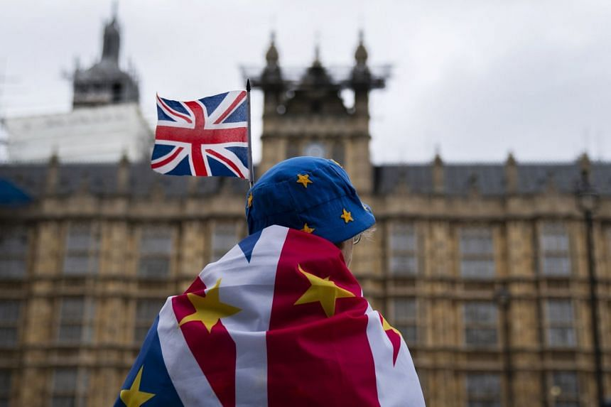 An anti-Brexit protester sits outside the Houses of Parliament, in central London.