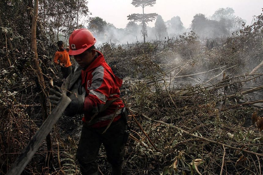 Indonesian firemen inspecting land in Kampar, Riau province, on Tuesday. More than a thousand hot spots have been spotted in Sumatra and Kalimantan. Malaysia saw its air quality worsen dramatically, with the air pollutant index in Rompin, Pahang, cli