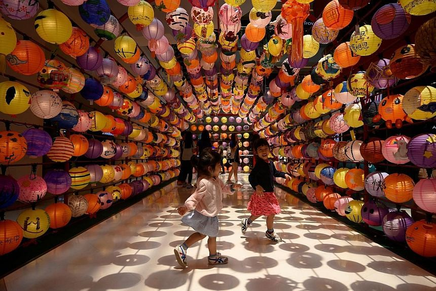 Children playing under a lantern installation at a shopping mall in Kuala Lumpur on Tuesday, ahead of tomorrow's Mid-Autumn Festival. The festival, meant to mark a bountiful harvest, is observed mainly by the Chinese. It is celebrated with eating moo