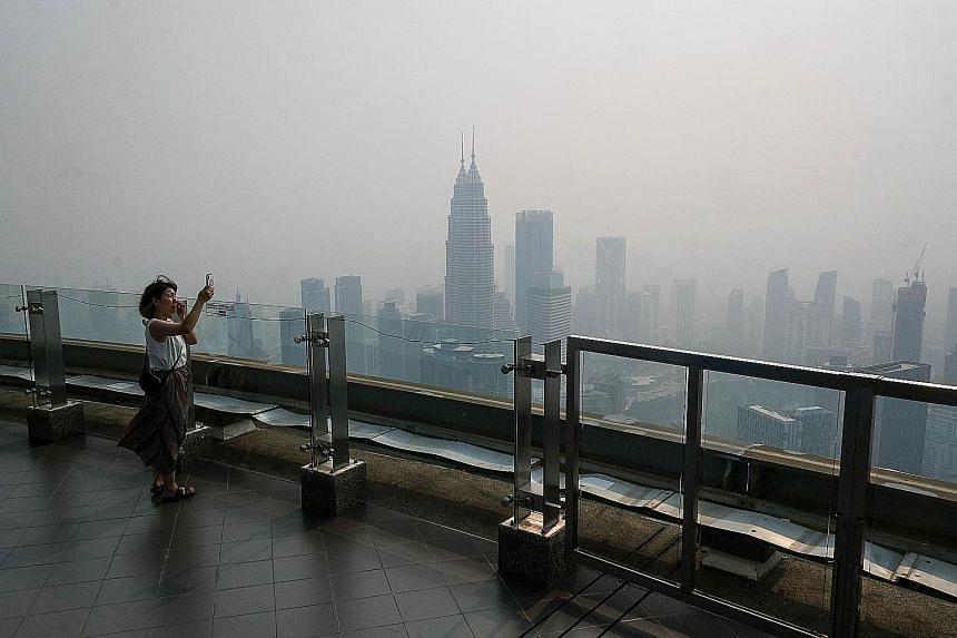 The Kuala Lumpur skyline obscured by thick haze yesterday as wind continued to blow haze coming from Kalimantan and Sumatra in Indonesia into Malaysian cities.
