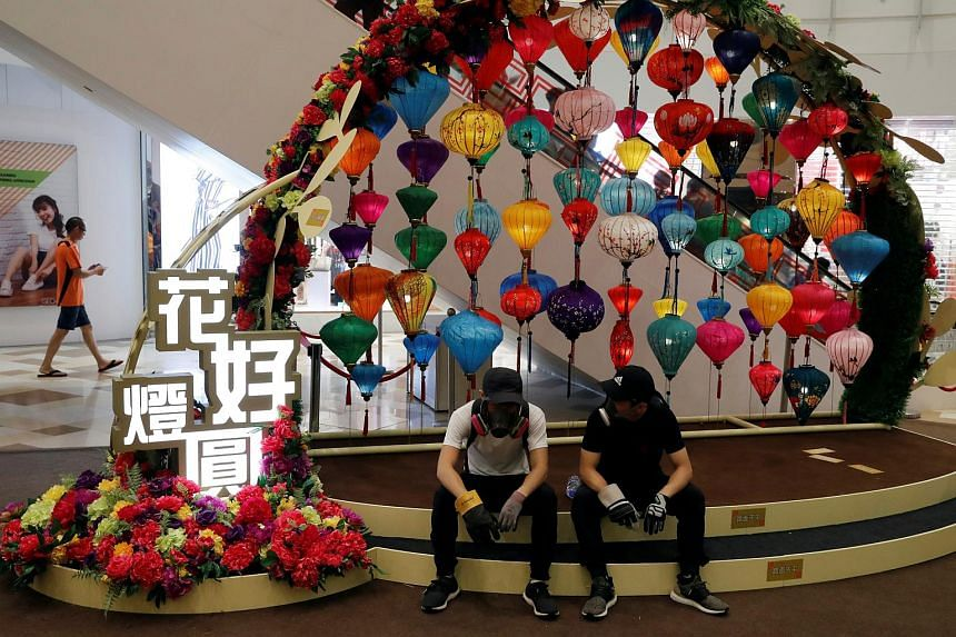 Protesters wearing gas masks rest in front of Mid-Autumn Festival decorations inside a shopping mall at Wong Tai Sin in Hong Kong on Aug 24, 2019.