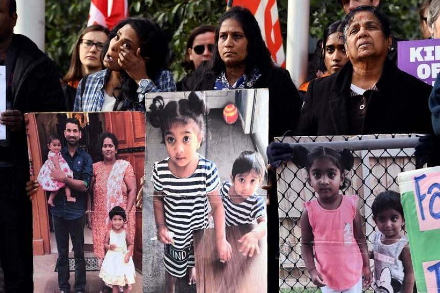 In a photo taken on Sept 4, people protest outside the Federal Court in Melbourne, where a hearing in a case has temporarily spared a Tamil family of four - including two Australian-born toddlers - from deportation and fuelled a political firestorm.