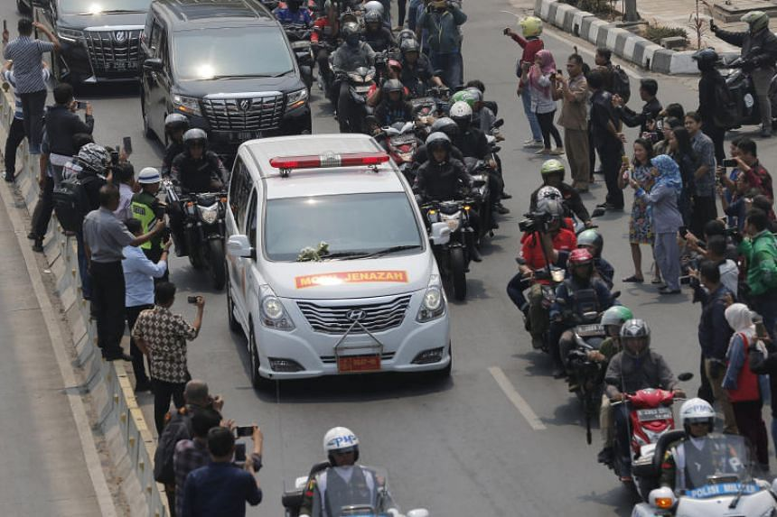 Thousands of mourners lined the streets of the capital, Jakarta, to watch the motorcade carrying the body of Indonesia's third president to the Kalibata heroes' cemetery.