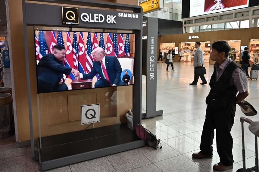 A man watches a news bulletin showing file footage of a meeting between US President Donald Trump and North Korean leader Kim Jong Un at the truce village of Panmunjom, at a railway station in Seoul on Sept 10, 2019.