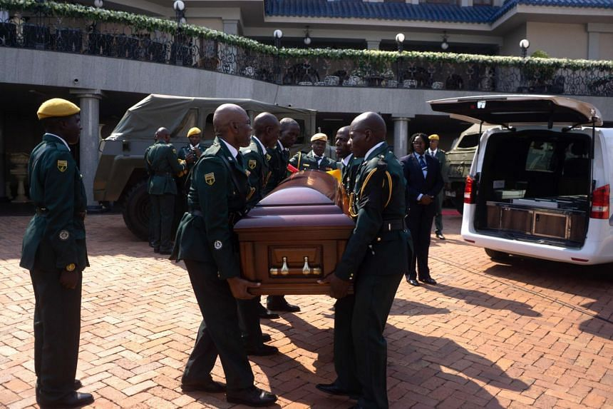 Pall bearers carry a casket holding the remains of the late former Zimbabwean president Robert Mugabe as they leave his Blue Roof Mansion for public viewing at the Rufaro Stadium in Harare