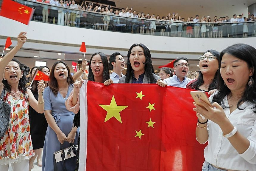 Pro-China supporters holding flags and singing the Chinese national anthem at a shopping mall in Hong Kong yesterday.