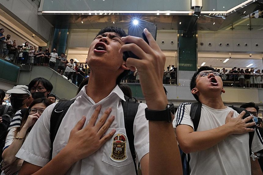 Protesters singing Glory To Hong Kong at a mall in the city on Wednesday. The anonymously penned tune, which first appeared on YouTube on Aug 31, has won a huge following among protesters.