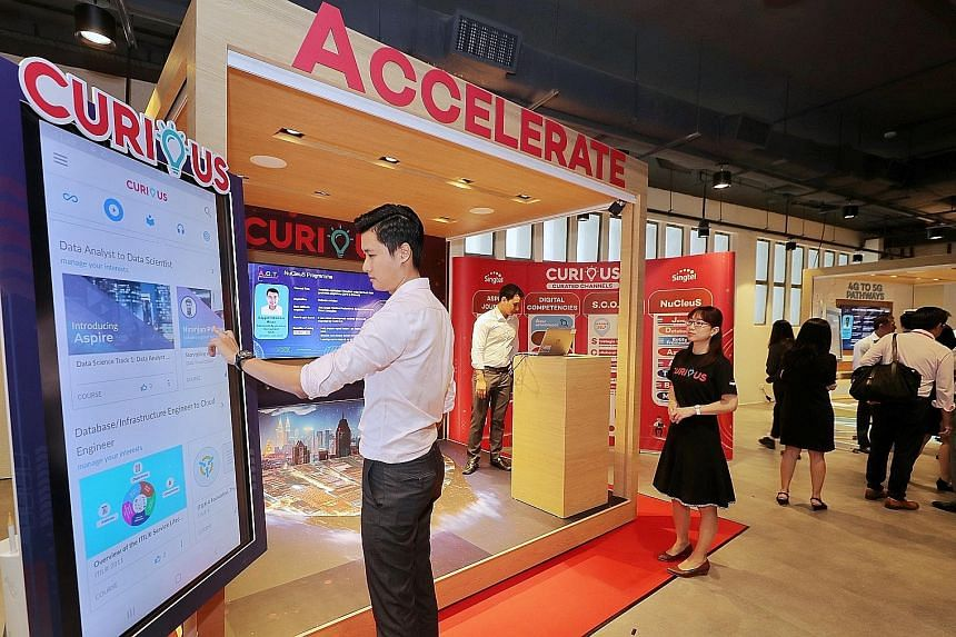 A staff member demonstrating Curious, Singtel's E-learning app for training and upskilling at the official opening of Singtel@8George yesterday. The four-storey office has classrooms, training facilities and interactive spaces for its staff to carry