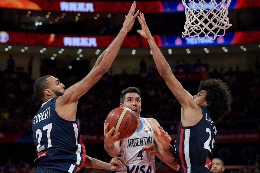 Argentina's Luis Scola going to the basket, as France's Rudy Gobert (left) and Louis Labeyrie try to block him in the Basketball World Cup semi-final in Beijing on Sept 13, 2019.