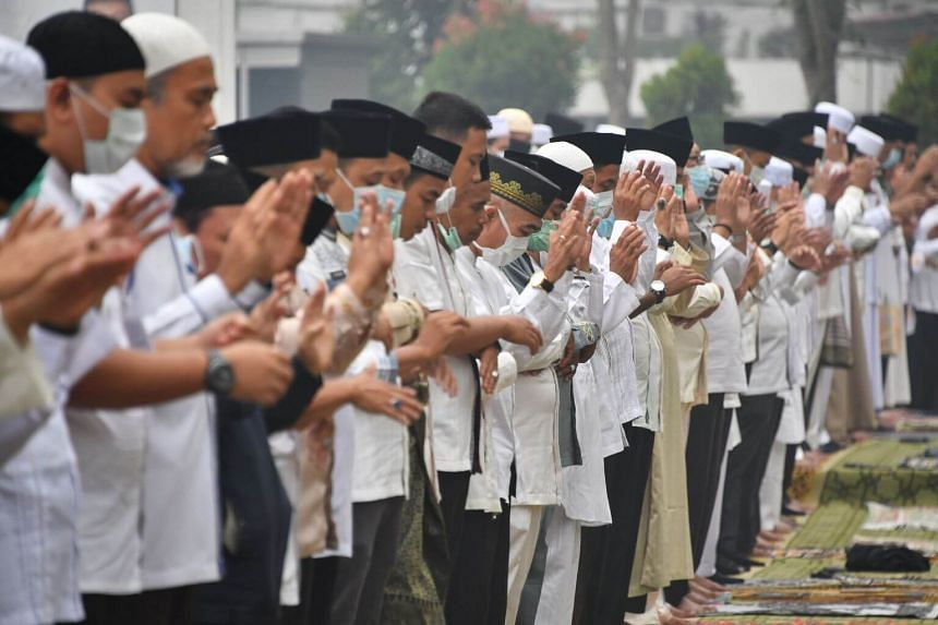 Around 1,000 of the city's residents - many dressed in white Muslim robes with rudimentary face masks - held a prayer on Friday in an open field as a thick, acrid haze drifted around them.