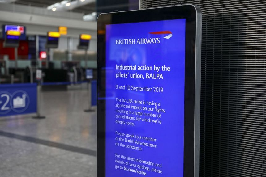 A digital information screen displays details of a strike by British Airways pilots at London's Heathrow Airport.