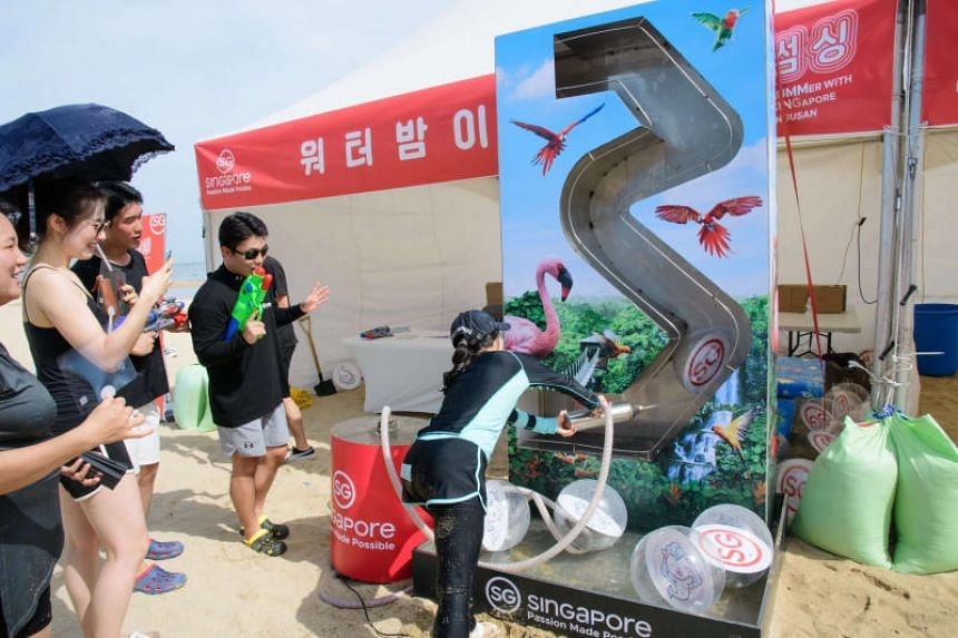 """Visitors playing a water bomb game during the """"Summer with Singapore in Busan"""" festival."""