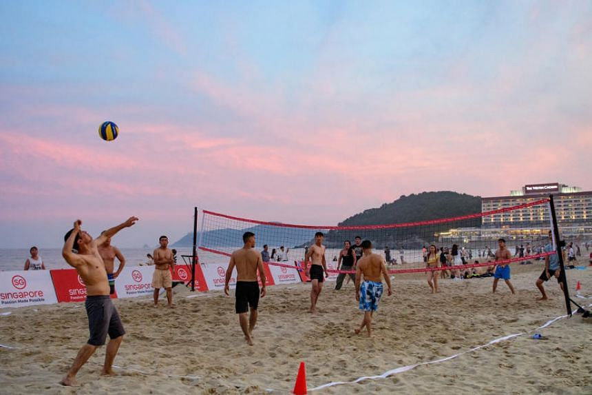 """Visitors playing beach volleyball during the """"Summer with Singapore in Busan"""" festival."""