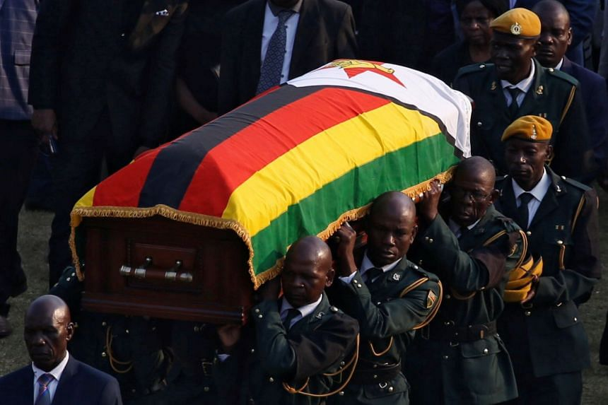 A casket carrying Mugabe's remains is carried to a military helicopter after his body lay in state at Rufaro stadium.