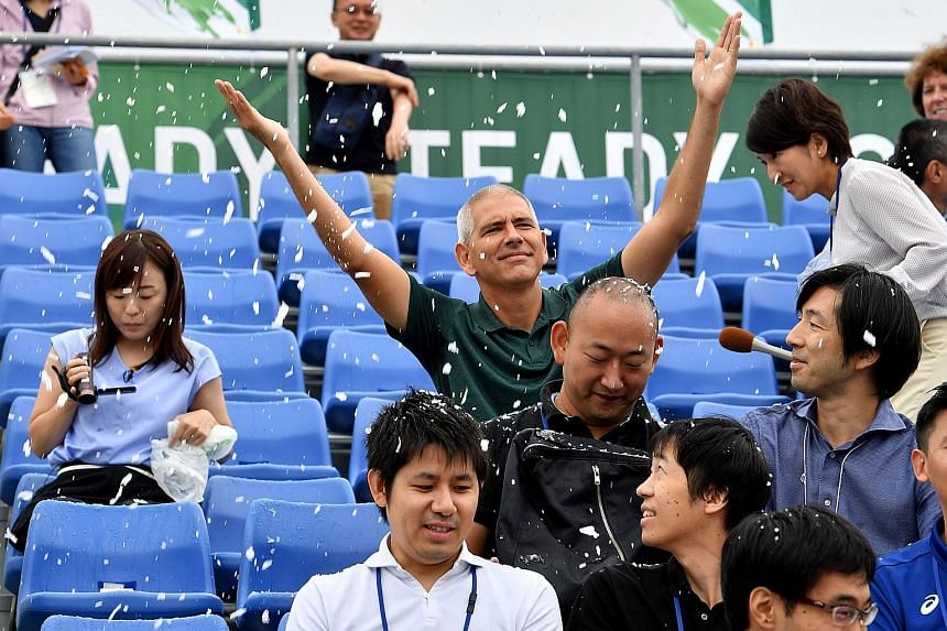 """Artificial snow falling on journalists during the Ready Steady Tokyo canoe sprint event, a test event ahead of the 2020 Olympic Games, in Tokyo yesterday. From pumping out cold mist to planting flower fences to """"psychologically"""" cool spectators, Toky"""