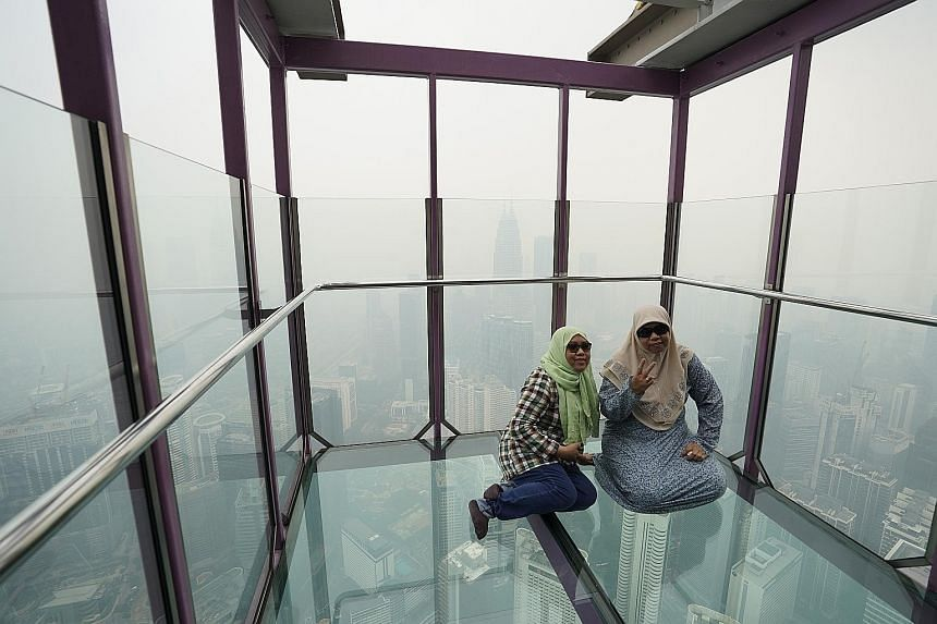 Tourists posing for a picture at the Skybox in the Kuala Lumpur Tower yesterday as the cityscape was shrouded in haze. The Selangor state government has decided to conduct cloud seeding in areas where the Air Pollutant Index reading exceeds the very