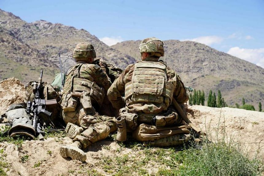 In a photo taken on June 6, US soldiers look out over hillsides at an Afghan checkpoint in Nerkh district of Wardak province.