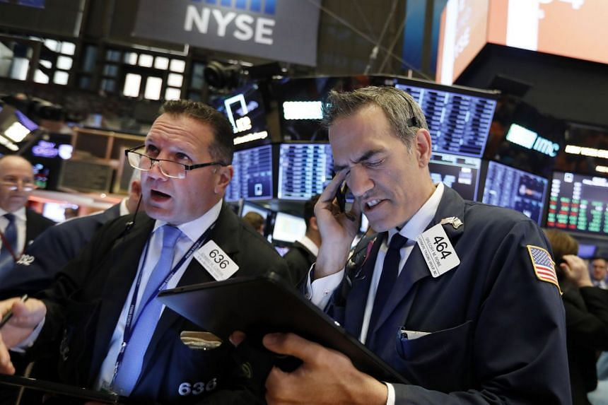 Traders Edward Curran (left) and Gregory Rowe work on the floor of the New York Stock Exchange.