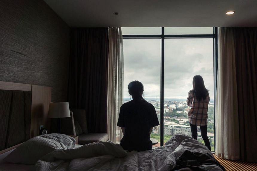 Kim Ye-na (left) and Lee Jin-hui, North Korean women who were forced to perform cybersex in China, look out from their hotel room in Vientiane, Laos, on Aug 22, 2019.