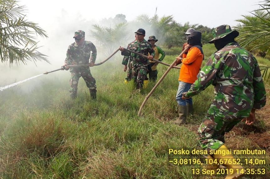 Military personel help ground firefighters in South Sumatra to douse raging fires.
