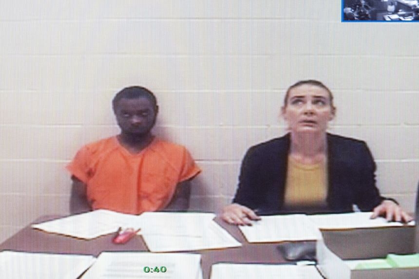 Tevin Biles-Thomas (left) shown on a video monitor, listens to his arraignment with public defender Alonda Bush.