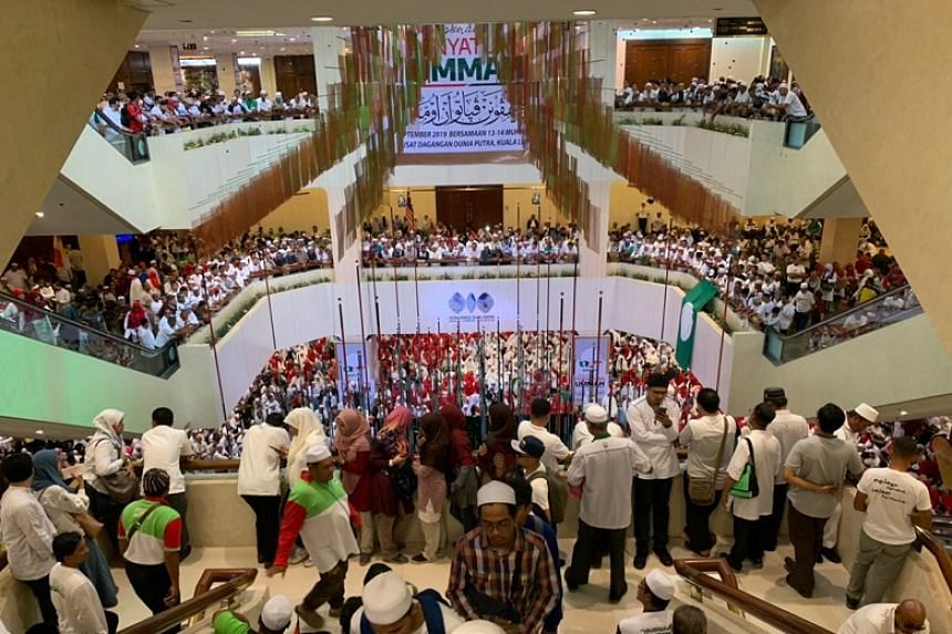 """Over 10,000 party faithful, most dressed in white, packed the Putra World Trade Centre to witness the chiefs of former rivals Umno and Parti Islam SeMalaysia sign a """"National Cooperation"""" charter outlining the terms of their pact on Sept 14, 2019."""