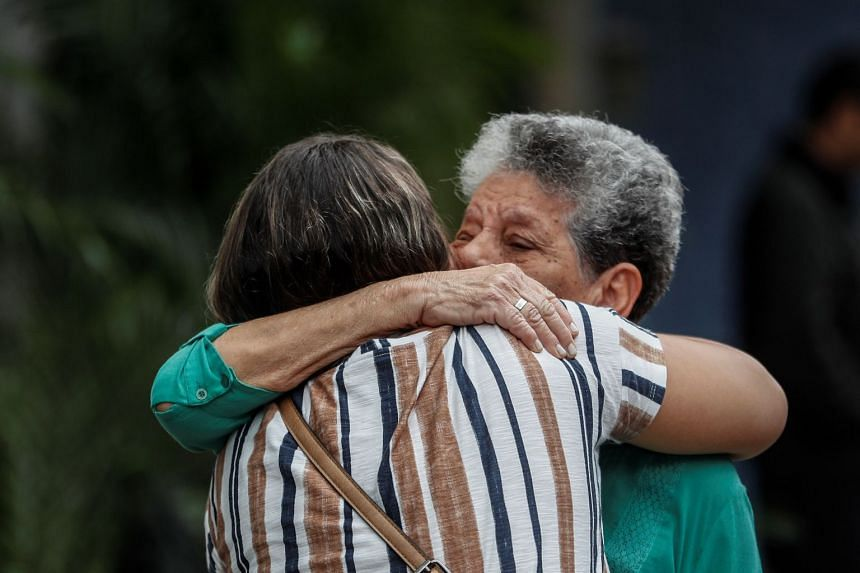 Two women cry in front of the Badim Hospital in Rio de Janeiro, Brazil.