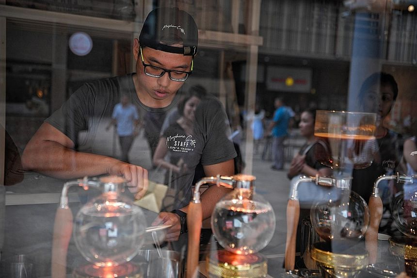 Morphine Coffee's co-founder Vester Sim brewing coffee with siphon coffee makers.