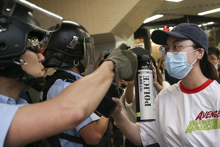 A police officer aiming pepper spray at a demonstrator as anti-government protesters and pro-China supporters scuffled inside a shopping mall in Hong Kong yesterday. Pro-China supporters fighting with anti-government protesters in the Kowloon Bay dis