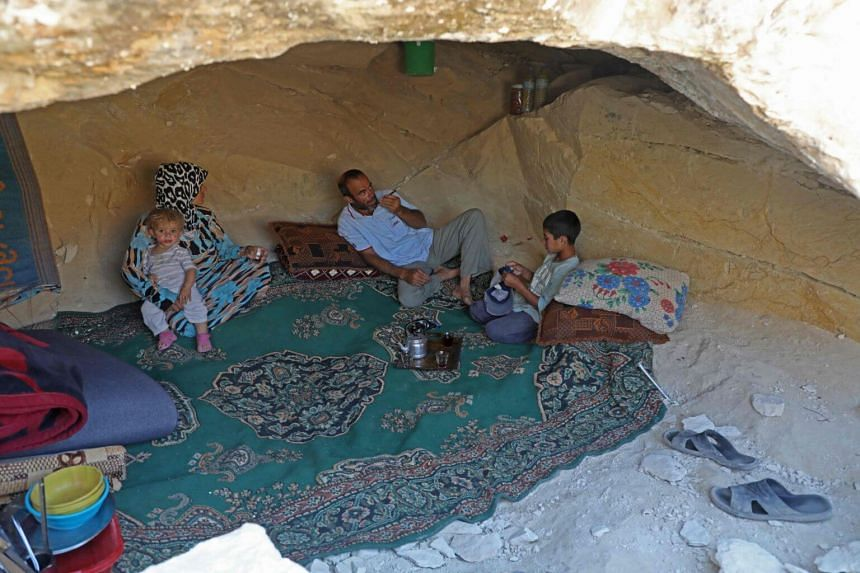 Abu Ahmad, a displaced Syrian from Termala sits with his family inside a cave he dug for shelter near the Syria-Turkey border, on Sept 9, 2019.