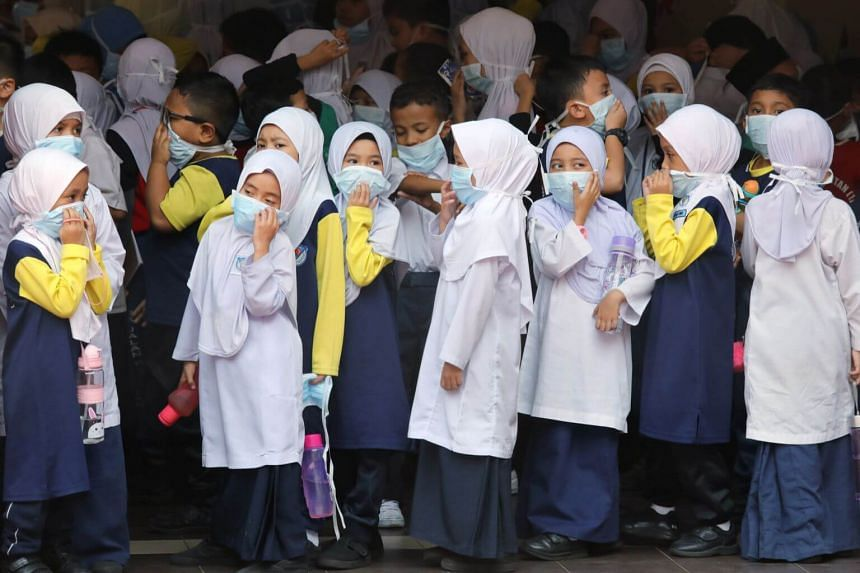 Students cover their faces with masks at a school as haze shrouds Kuala Lumpur, on Sept 13, 2019.