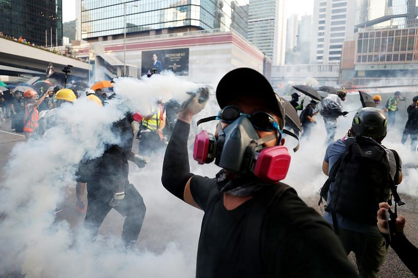 An anti-government protester throwing a tear gas canister back at the police during a demonstration near Central Government Complex in Hong Kong on Sept 15, 2019.