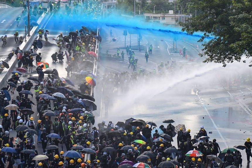 Pro-democracy protesters getting hit by water cannons outside the government headquarters in Hong Kong on Sept 15, 2019.