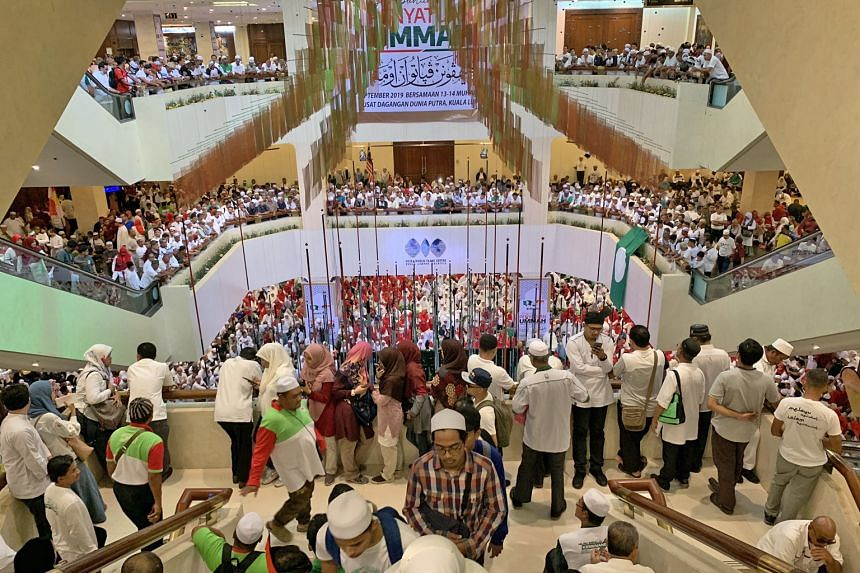 Umno president Zahid Hamidi (left) joining hands with PAS president Hadi Awang at yesterday's Ummah Unity Gathering in Kuala Lumpur. PHOTO: REUTERS More than 10,000 party faithful, many dressed in white, at the Putra World Trade Centre yesterday to w