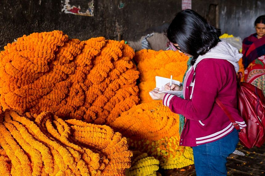 A participant of a walking tour takes in the sights at Kolkata's Mallick Ghat flower market.