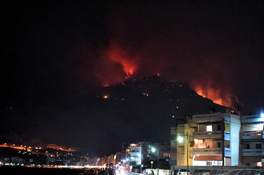 Flames are seen from a forest fire burning near the Greek seaside town of Loutraki on Sept 14, 2019.