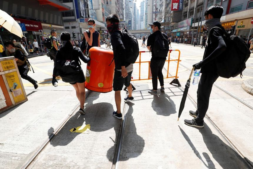 Anti-government demonstrators carrying a barrier and a garbage bin during a protest in Causeway Bay on Sept 15, 2019.