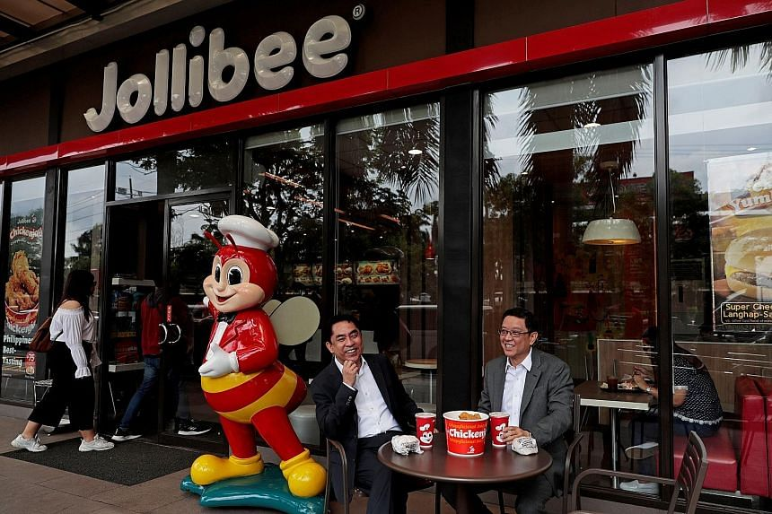 Jollibee Foods Corp chief executive Ernesto Tanmantiong and chief financial officer Ysmael Baysa (far left) outside a Jollibee branch in Pasig City, Metro Manila, Philippines, in July.