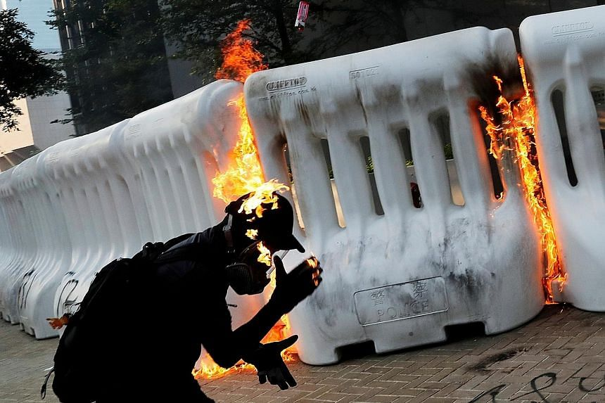Police using water cannon outside the government headquarters in Hong Kong to disperse protesters yesterday. One water cannon was spraying blue jets of water, which make protesters easier to identify later. A protester on fire after throwing a Moloto