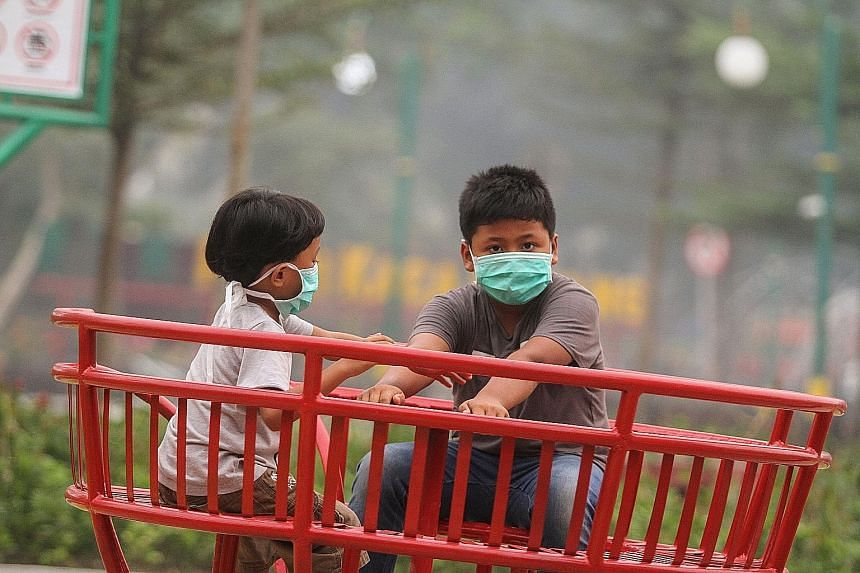 Indonesian children wearing masks at a playground in Pekanbaru, Riau province, on Saturday as the air quality worsened. In response to the haze, the Riau government has temporarily suspended activities at schools.