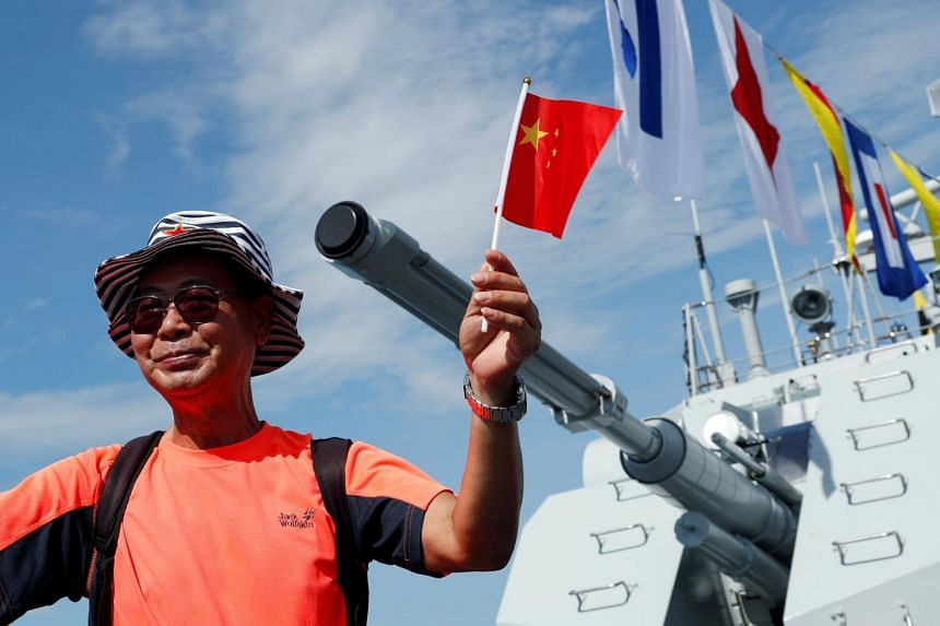 In a photo taken on June 30, 2019, a visitor holds a Chinese national flag as he poses for a photo on the deck of navy ship. The Chinese shipbuilder did not provide details about the ship's specifications, or its construction and delivery schedule to