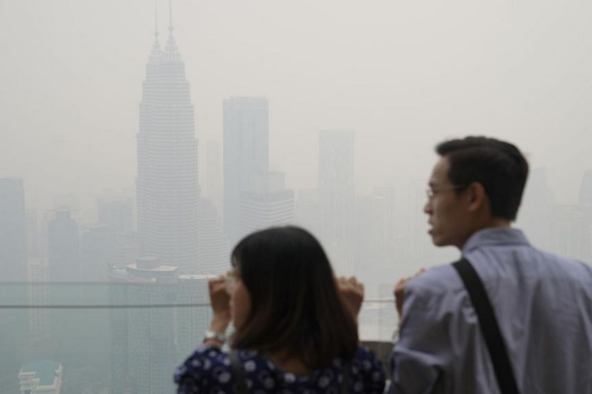 Tourists look out from the Kuala Lumpur Tower during a hazy day in the Malaysian capital, on Sept 13, 2019.