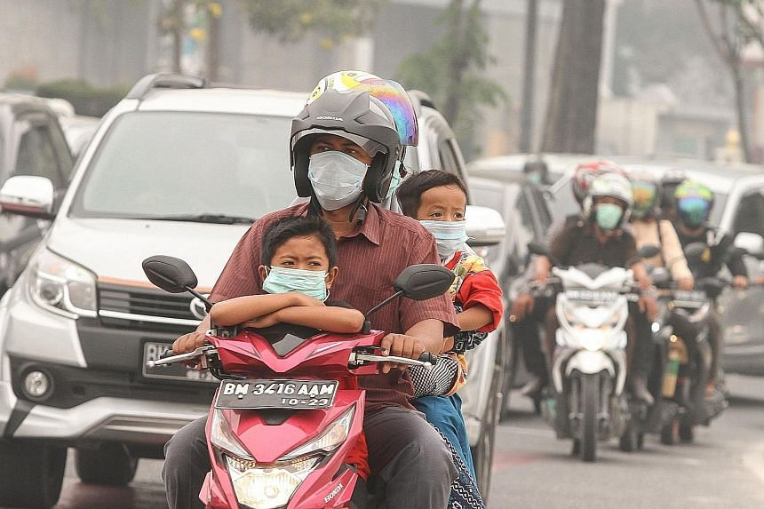 Residents in Pekanbaru, in Riau province, wearing masks to protect themselves. The city's PM10 PSI reading surged to 385 at 8pm yesterday. PHOTO: EPA-EFE
