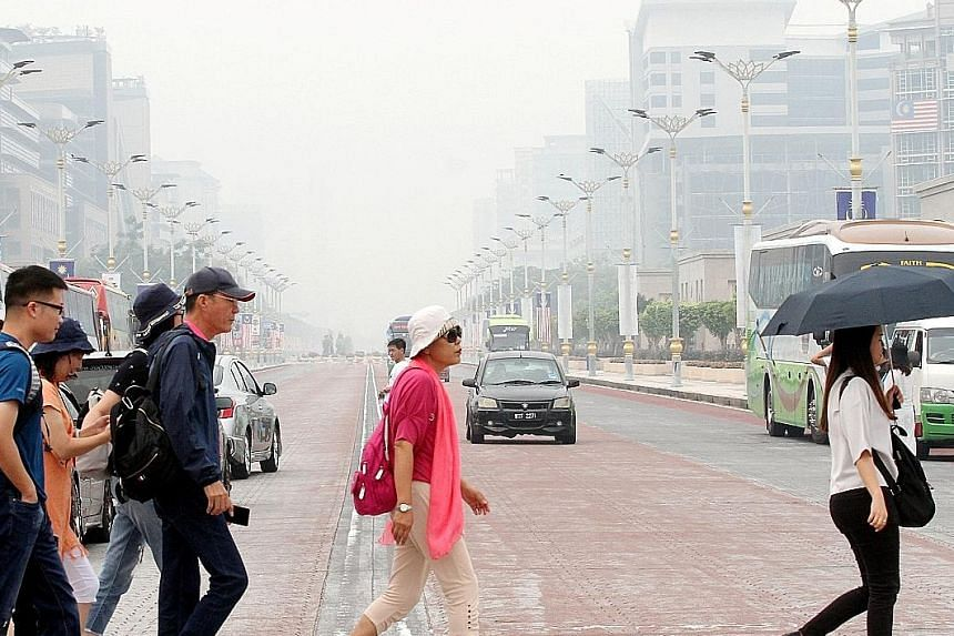 Hazy conditions in the administrative capital Putrajaya at around 11.30am yesterday. A total of 25 schools in the city are expected to shut today. PHOTO: THE STAR/ASIA NEWS NETWORK